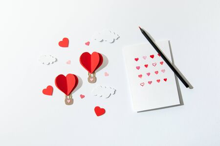 Foto de top view of greeting card with hearts and pencil near paper heart shaped air balloons in clouds on white background - Imagen libre de derechos