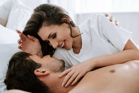 Photo pour selective focus of happy girl lying with handsome man on bed - image libre de droit