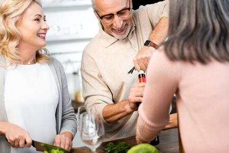 Photo pour selective focus of man opening bottle with wine and woman cutting lettuce - image libre de droit
