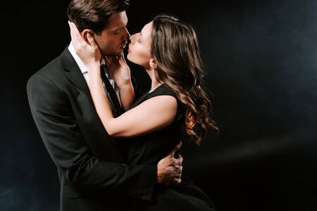 Photo pour side view of woman in dress kissing with handsome man on black - image libre de droit