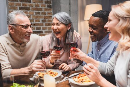 Photo pour smiling multicultural friends talking and clinking with wine glasses during dinner - image libre de droit