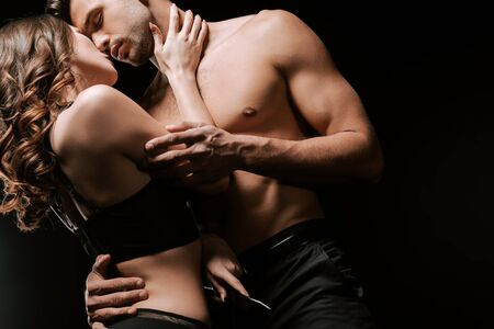 Photo pour low angle view of woman touching sexy man isolated on black - image libre de droit