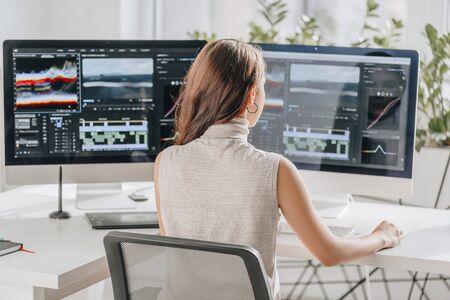Photo pour back view of filmmaker working near computer monitors - image libre de droit