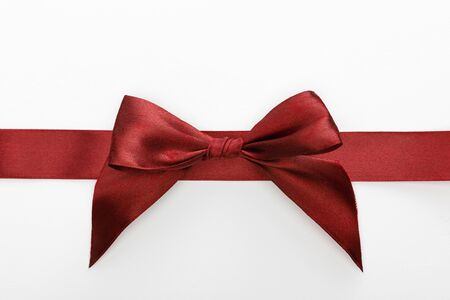 Photo pour top view of satin burgundy decorative ribbon with bow isolated on white - image libre de droit