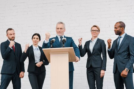 Photo pour happy speaker in glasses and multicultural businessmen and businesswomen showing clenched fists - image libre de droit