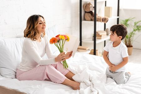 Photo pour happy woman holding flowers and looking at mothers day card while sitting in bed near adorable son - image libre de droit