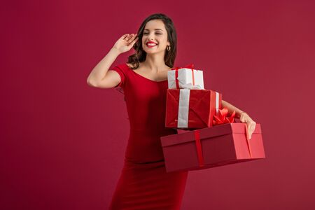 Photo for sexy, happy girl looking away and waving hand while holding gift boxes isolated on red - Royalty Free Image