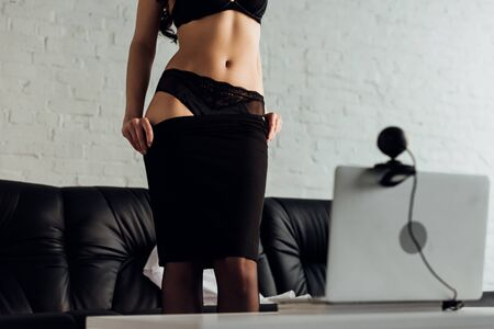 Photo pour Selective focus of beautiful girl taking off skirt in front of web camera, cropped view - image libre de droit