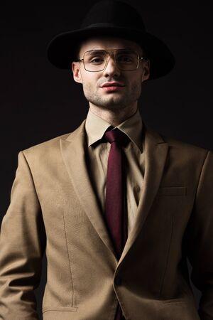 Photo pour confident elegant man in beige suit, hat and eyeglasses isolated on black - image libre de droit
