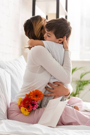 Foto de happy mother hugging adorable son while sitting in bed near flowers and mothers day card - Imagen libre de derechos