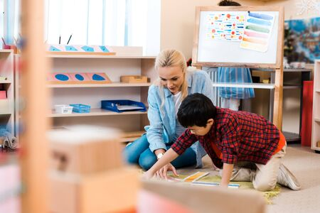 Selective focus of teacher playing with kid in montessori school