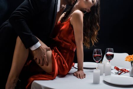 Photo pour Cropped view of man in suit holding hip of beautiful woman on served table with wine isolated on black - image libre de droit