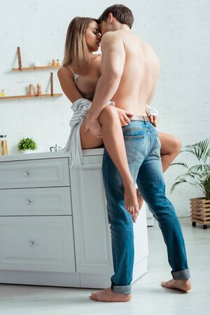 Photo pour shirtless man kissing sexy woman with big breast and barefoot - image libre de droit