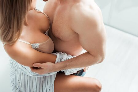 Photo pour cropped view of shirtless man touching hot woman in underwear - image libre de droit
