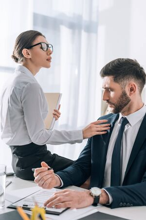 Photo pour attractive secretary sitting on table and touching businessman in office - image libre de droit