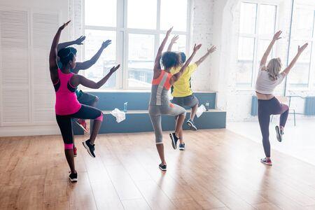 Photo pour Back view of multicultural dancers exercising in dance studio - image libre de droit
