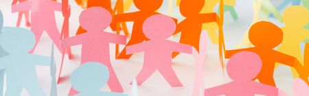 Foto de panoramic shot of colorful paper cut chain people on white, human rights concept - Imagen libre de derechos