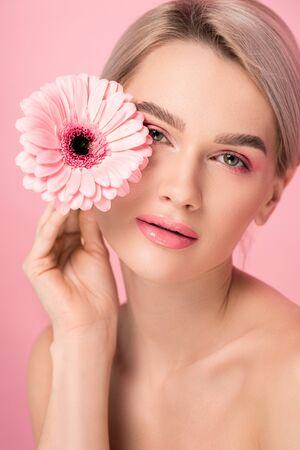 Foto de tender naked woman with pink makeup holding gerbera flower, isolated on pink - Imagen libre de derechos