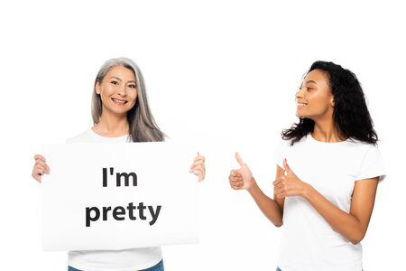 Photo pour happy african american woman showing thumb up near i`m pretty placard isolated on white - image libre de droit