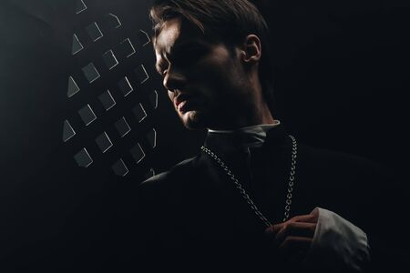 Photo pour young serious catholic priest touching cross on his necklace in dark near confessional grille - image libre de droit