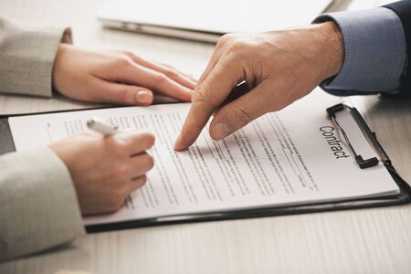 Photo pour cropped view of realtor pointing with finger at clipboard with contract lettering near woman - image libre de droit