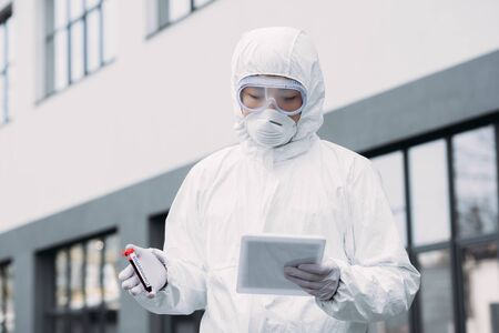 Photo pour asian epidemiologist in hazmat suit and respirator mask using digital tablet while holding test tube with blood sample on street - image libre de droit