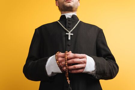 Photo pour low angle view of catholic priest holding wooden rosary beads isolated on yellow - image libre de droit