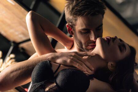 Photo pour low angle view of boyfriend kissing and hugging girlfriend in black bra - image libre de droit