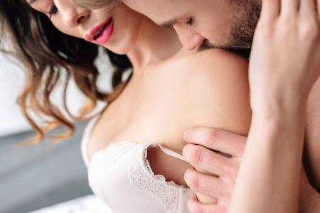 Photo pour cropped view of boyfriend kissing sexy girlfriend in white bra - image libre de droit