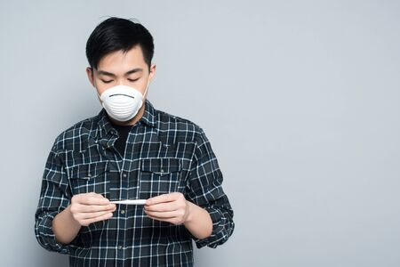 Photo pour young asian man in respirator mask looking at thermometer on grey background - image libre de droit