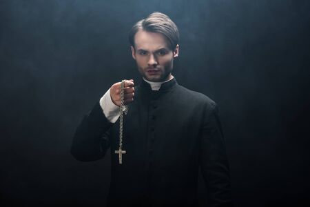 Photo pour confident catholic priest holding necklace with cross while looking at camera on black background with smoke - image libre de droit