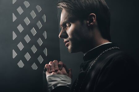 Photo for young thoughtful catholic priest praying with closed eyes in dark near confessional grille with rays of light - Royalty Free Image