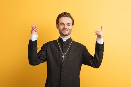 Photo pour smiling catholic priest pointing up with fingers while looking at camera isolated on yellow - image libre de droit