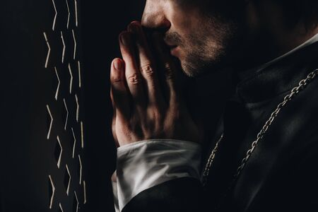 Photo pour cropped view of catholic priest praying near confessional grille in dark with rays of light - image libre de droit