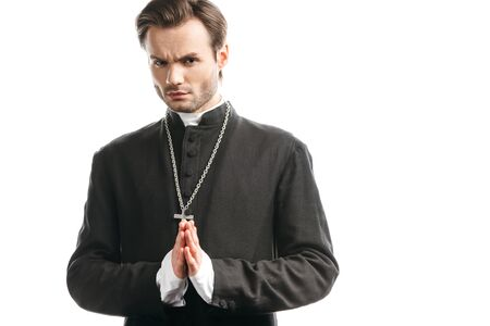 Photo pour serious, strict catholic priest with praying hands looking at camera isolated on white - image libre de droit