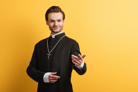 Photo pour smiling catholic priest standing with outstretched hand while looking away isolated on yellow - image libre de droit