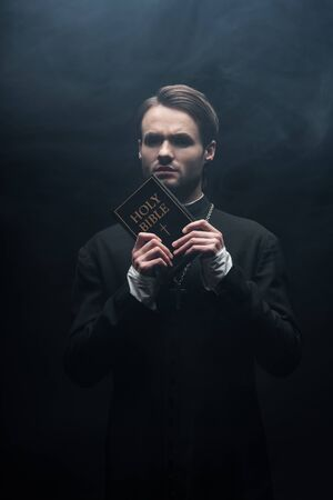 Photo pour tense catholic priest looking at camera while holding holy bible on black background with smoke - image libre de droit