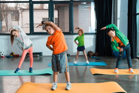 Photo for Selective focus of multicultural children warming up together on fitness mats in gym - Royalty Free Image