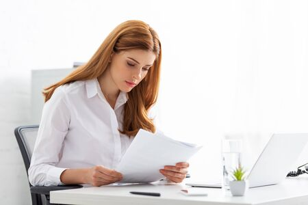 Photo pour Successful businesswoman holding papers with charts at table in office - image libre de droit