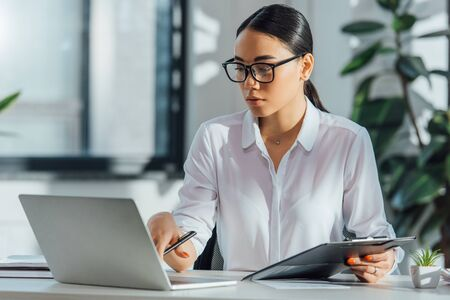 Photo pour asian translator in eyeglasses working online with laptop in office - image libre de droit