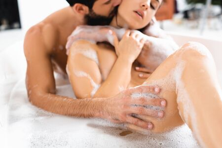 Photo pour Selective focus of handsome man kissing and touching sexy girlfriend in bathtub with lather - image libre de droit