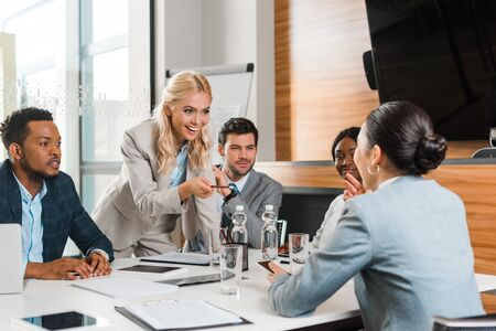 Photo pour young smiling businesswoman pointing with pencil near multicultural colleagues sitting at desk in conference hall - image libre de droit