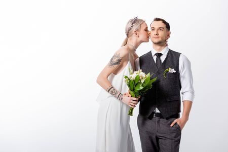 Photo pour beautiful tattooed bride kissing handsome bridegroom isolated on white - image libre de droit