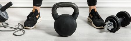 Photo for panoramic shot of sportswoman with kettlebell and sports stuff standing at home - Royalty Free Image