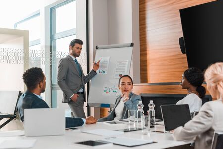 Photo pour handsome businessman pointing with finger at flipchart with infographics while multicultural colleagues sitting at desk in conference hall - image libre de droit