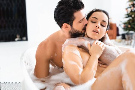 Photo pour Handsome man kissing and embracing naked girlfriend while taking bath together - image libre de droit