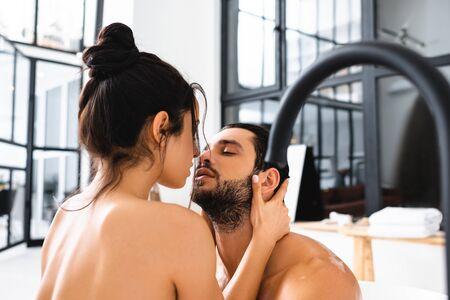 Photo pour Beautiful naked woman kissing handsome boyfriend in bathtub - image libre de droit