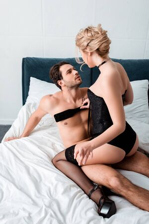 Photo for seductive woman holding spanking paddle and sitting on submissive man - Royalty Free Image