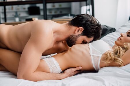 Photo pour Side view of handsome man kissing belly of sexy girlfriend on bed in bedroom - image libre de droit