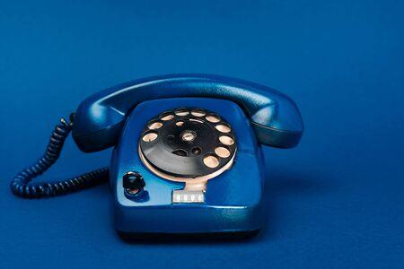 Foto de bright and colorful retro telephone on blue background - Imagen libre de derechos